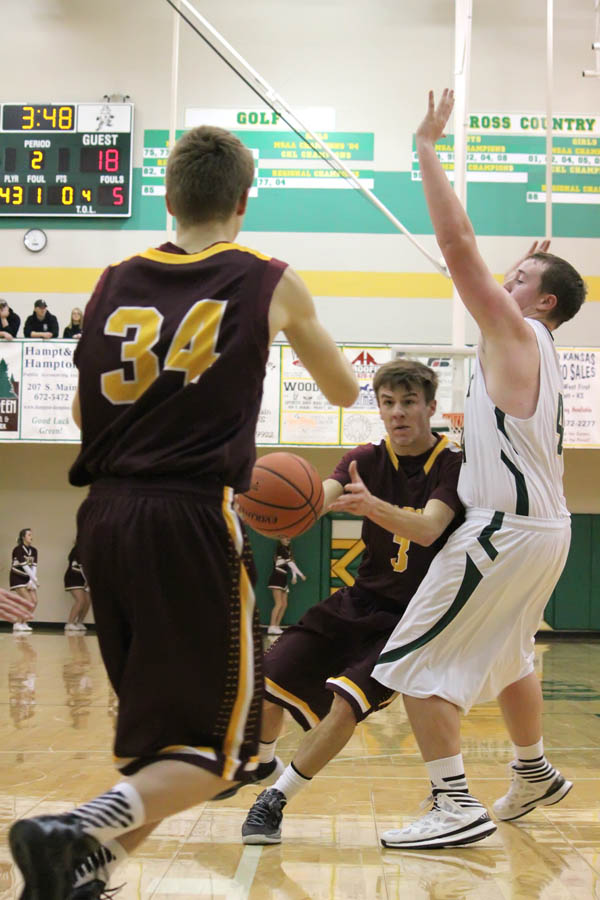 Hillsboro?s Evan Ollenburger shovels a pass in the lane to teammate Micah Allen, who scored easily on the play during Friday?s game at Pratt. The Trojans struggled offensively for much of the night, dropping a 48-47 game to the Greenbacks for Hillsboro?s first loss of the season.