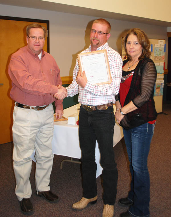 Rickey Roberts, K-State extension agent for Marion County, presents a Banker Award to Greg and Ronda Wiens of Hillsboro.