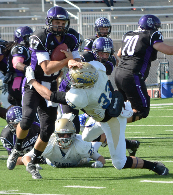 Michael Griffin tackles Southwestern quarterback Tyler Crandall for a 2-yard loss late in the third quarter Saturday. Tabor lost the game to the Moundbuilders, 27-6.