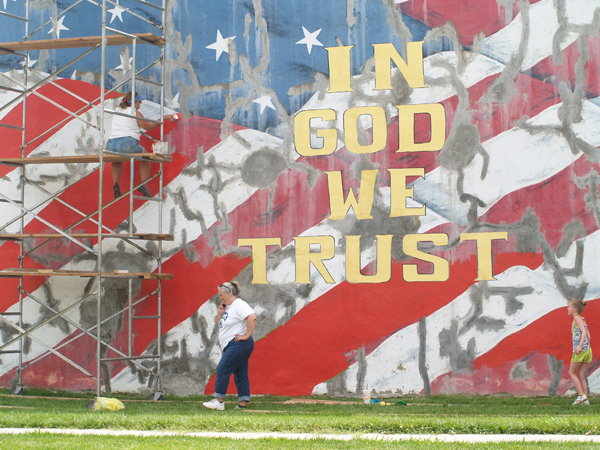 Three Marion County volunteers?Joy Waldbaurer on scaffolding and Skye Young (walking) and Alyssa Young on the ground?repainted the huge American Flag mural at Liberty Park in Marion during July. Patty Decker photos