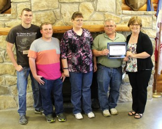 Renee Lippincott (far right) of KDOC?s south-central Kansas regional office presents the Award of Merit to the Franz family (from left) Ryan, Darren, Melanie and Dale. Free Press photos by Don Ratzlaff