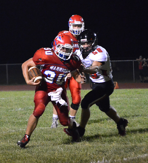 Aaron Riggs carries the ball during the second half of Marion?s season-opening game against Moundridge Friday. Riggs was the Warriors? leading rusher with 23 carries for 150 yards in Marion?s 24-14 win.