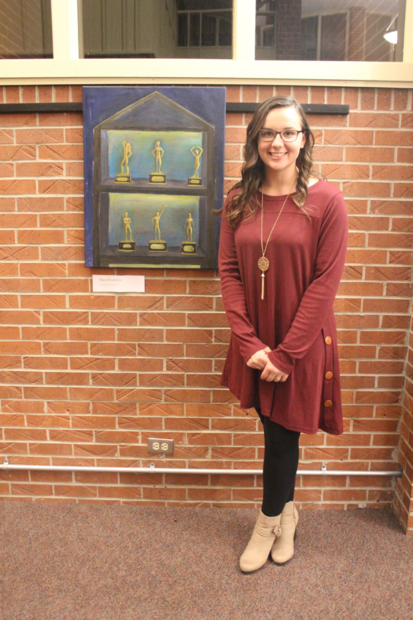 Chloe Lind, who has participated in Dressember for years, stands by one of her pieces that she created regarding the objectification of women. She presented her art at a kick-off for Tabor College's Social Justice Dressember participation.