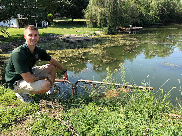 Isaac Hett, superintendent at Marion County Park and Lake, sits next to Stone Arch Cove where the grass-eating carp were released. In just two months since the carp were released the moss and algae have cleared substantially. Patty Decker/Free Press