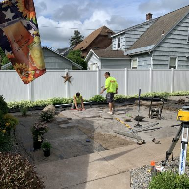 2 people installing pavers for a patio
