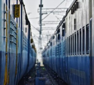 two indian trains parked next to each other