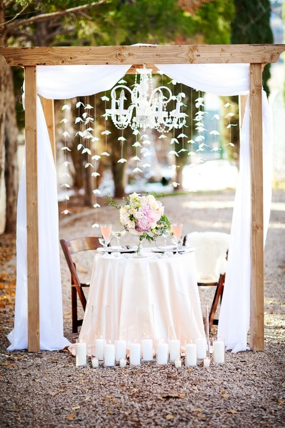 Sweetheart Table Under An Arch With A Chandelier Peach Wedding
