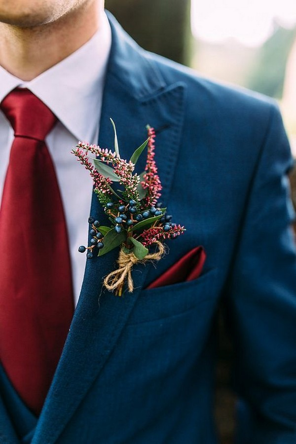 navy fall and winter groom wedding suit and burgundy boutonniere