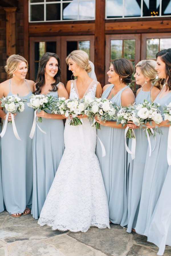 Bridesmaids in steel blue dresses with white and green bouquets