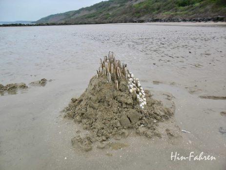 Mit Muscheln geschmückte Sandburg am Strand von Houlgate