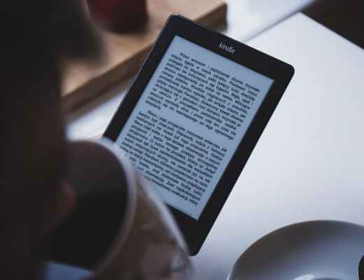person using e book reader while drinking coffee
