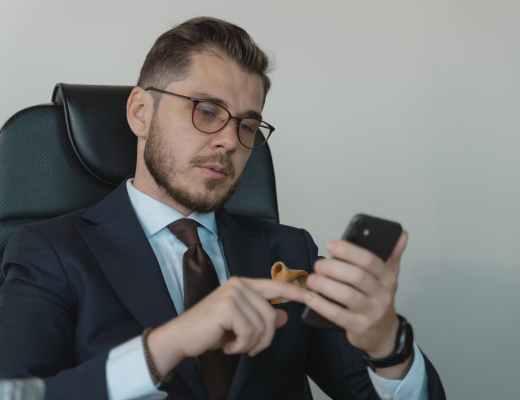 man in black suit jacket holding black smartphone