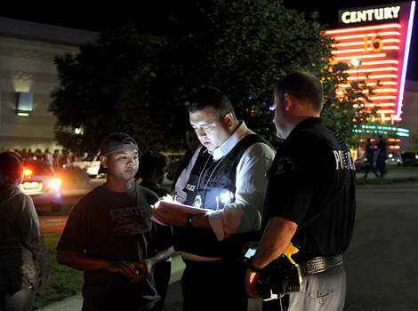 An Aurora Police Department detective takes a witness statement following a shooting outside the 16 movie theatre in Aurora. Aurora Police responded to the Century 16 movie theatre where police confirm at least 14 people are dead and 50 others injured. AP Photo/Karl Gehring Shooting at Batman screening