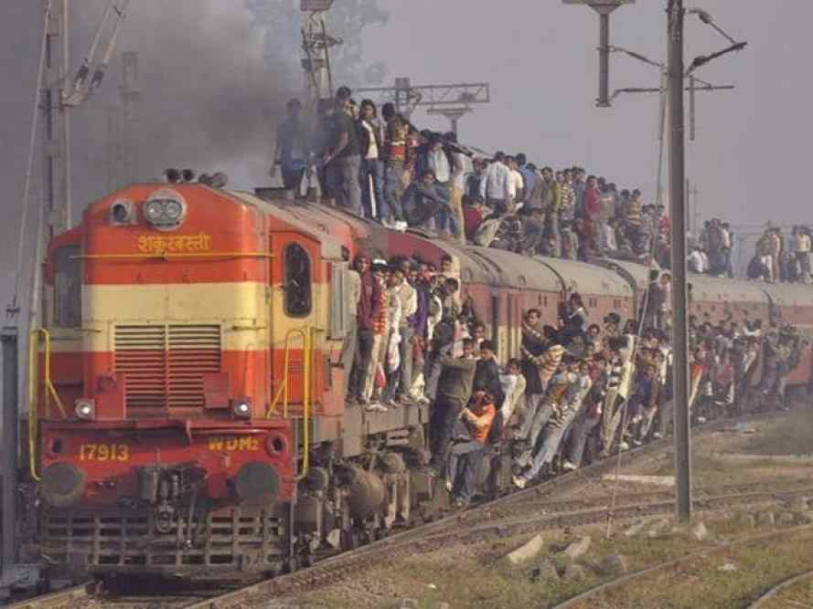 A red train chuffing on the tracks with hundreds of people standing on the roof and hanging onto the size