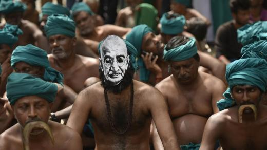 Tamil Nadu Farmers enacts eating a snake as a form of protest as one of them wears a mask with the face of Mahatma Gandhi. (Ravi Choudhary/HT PHOTO)