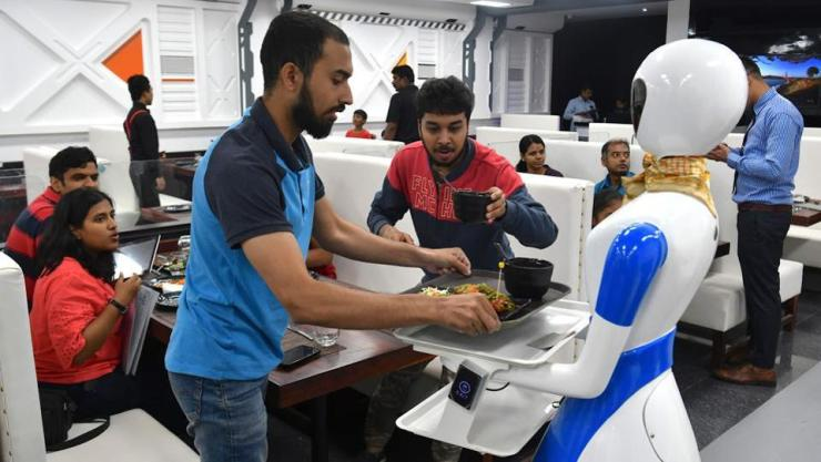 A service robot delivers food to customers. On a digitally marked out path the robot heads out with the food neatly arranged on a tray. At the assigned table, she turns to greet and guide the customer to pick up the dish. (Manjunath Kiran / AFP)
