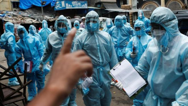 Healthcare workers wait to take off their personal protective equipment (PPE) after the end of a check-up camp for the coronavirus disease (Covid-19) at a slum in Mumbai.
