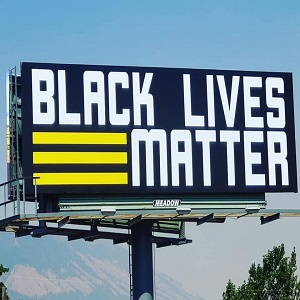 """Maria PistolWhiplash Carmichael decided to do something to further the BLM cause. She is a native of Oregon, which is the home of Portland, where protests have turned violent, and people are fighting military police. Long before that, Maria launched a fund going towards purchasing a billboard to place """"Black Lives Matter"""" on it. Finally, the billboard has come to light, and she is showing it off on Facebook, where it's been well-received."""