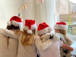 4 kids voor de kerstboom met kerstmutsen kerstkaart