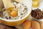 chocolate chip cookie ingredients mix and egg in a bowl with bowl of chips