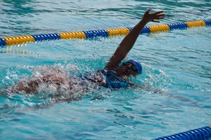 african american young woman in pool doing backstroke