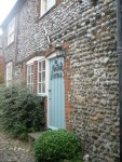 anchor cottage old stone building with robins egg blue door and name in iron