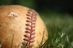 old, tattered baseball in field of grass, lonely