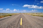 wide angle of empty new mexico road with bright skies and few clouds