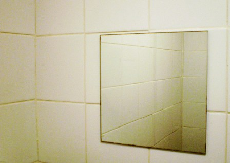 small square mirror in tiled bathroom