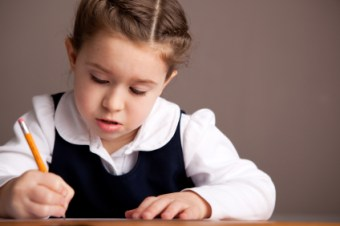 school girl in uniform writing at desk about 7 years old