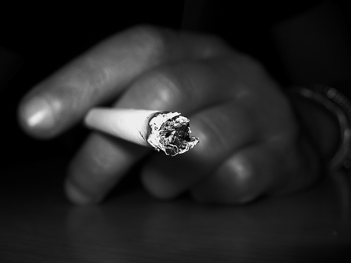 close up of lit cigarette about to ash, male hand