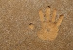 kid's hand print in the sand
