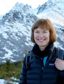 susan pope hiking with mountains behind her