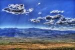 sun shining through clouds over catalina mountains