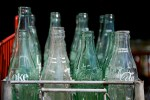 old coke bottles in recycling crate
