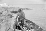 inuit man in canoe with fish with iceberg in back
