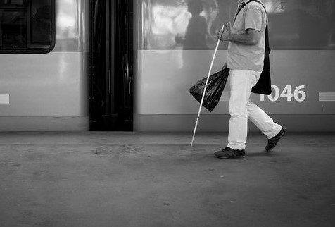 train car with door open; man with cane, picture from shoulders down, coming into frame from right
