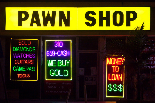 exterior of pawn shop neon lights advertising cash for things