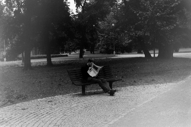 man reading paper in park