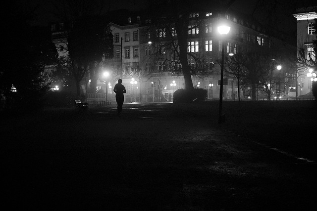 woman running under street light, seen from a distance, dark and shadowy