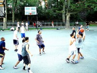 crowd of younger adults and teens playing basketball, several races together