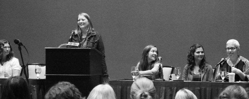 writers at a head table woman at podium