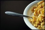 bowl of corn flakes off center, spoon sticking otu