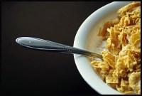 bowl of corn flakes off center, spoon sticking otu