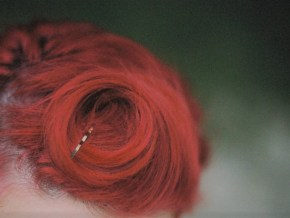 close-up shot of dyed bright red hair, with a wisp of curl bobby-pinned