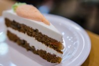 single slice of carrot cake on plate, carrot-shaped design made of icing