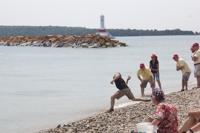 The actual competition, men tossing stones on shore