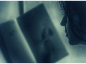 close up of woman looking into a book and holding it in front of her face