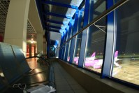 empty airline gate waiting area at night, planes lined up outside window