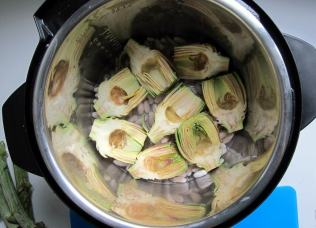 Pressure cooker filled with artichokes and beans, ready to go.
